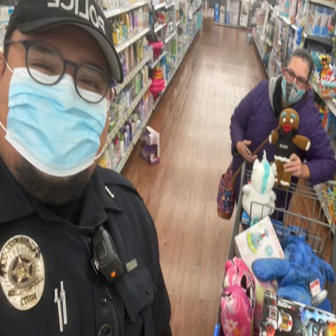 police officer and woman in mask holding a gingerbread stuffed animal