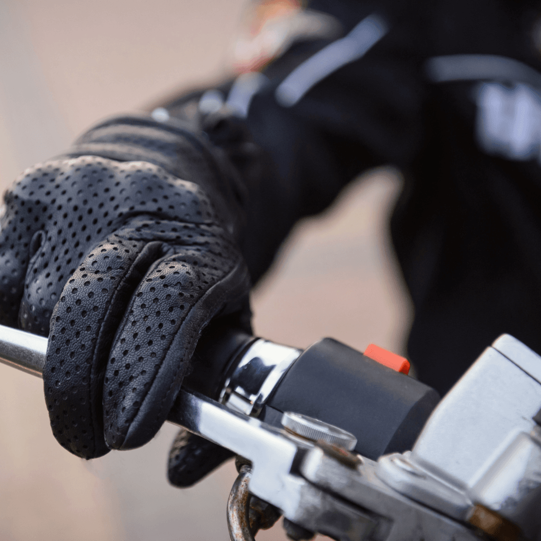 gloved hand gripping motorcycle handlebar